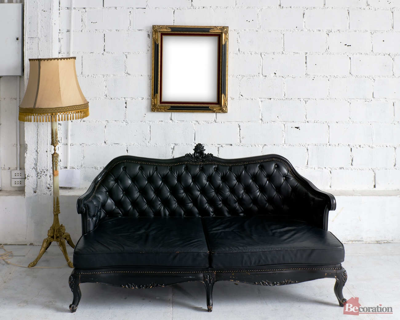 Old black leather sofa with lamp and wood picture frame